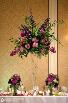 Pink and purple wedding centerpiece in a tall glass vase