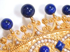 Crown Style Comb of goldwork, Lapis Lazuli and Pearls.  Date: Circa 1850.  A Victorian era hair comb, fit for HM Queen Victoria, is crafted from 18k yellow gold and decorated with natural pearls and gems of lapis lazuli. The comb itself is of natural tortoise shell of variegated shades of brown and touches of blonde. Fabricated in the shape of a crown scores of scrolls and twisted gold wire work abound. A trio of navette shapes is accented with lustrous creamy white natural pearls which…