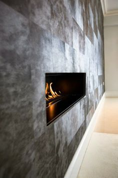 Contemporary fireplace set within a textured feature wall