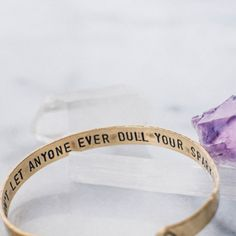 "Make a statement on your arm and set an intention in your heart with this inspirational quote bracelet. The inside of the bracelet reads, ""Don't let anyone ever dull your sparkle."" Diamond shapes are featured on the outside ends."
