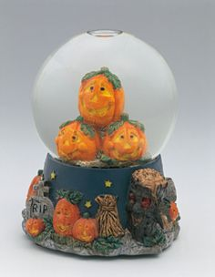Close-up of figurines of Halloween pumpkins in a snow globe