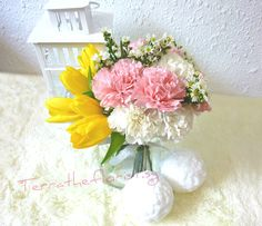 Styled with carnations, tulips, wax flowers, daisies, and other accents.
