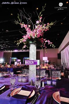 Sabella Berman Events used  tall orchid centerpieces on the four corners of the ballroom in a NY themed party to define the space.  In the vase we used purple LEDs, crinkle cello and water to give a crushed ice effect. Two other centerpieces were used on a collection of over 16 tables. Each unique, with a NY themed street name on mini tabletop lampposts.