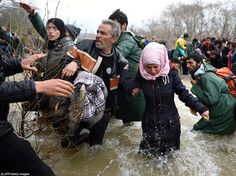 Refugees and migrants try to cross a river on their way to Macedonia from a makeshift camp at the Greek-Macedonian border, near the Greek village of Idomeni, on March 14 after thousands were stranded by the Balkan border blockade