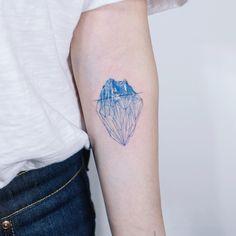 Colorful geometric iceberg tattoo idea on arm