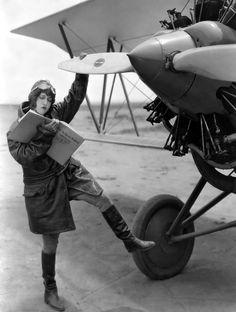 silent film actress Dorothy Sebastian mugs with a biplane