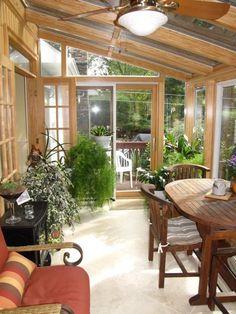 véranda bois et verre- salle à manger, canapé et plantes vertes en pots