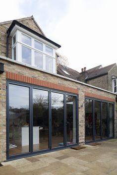 Rear extension | brick | flat roof | hidden drainage | parapet upstand | grey alumuminium bi-fold doors | patio | stone coping