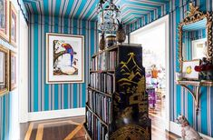 "Inside the stunning home of the Ultimate A-list decorator: Alex Papachristidis. ""I thought that the colors were so wonderful and whimsical,"" Alex says of the striped Lee Jofa fabric in the entryway. He found the double-sided bookcase while antiquing in Hudson, NY. ""There's nothing I like more than books."" Photo by Lesley Unruh. One Kings Lane Designer Houses."