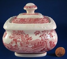 This is a Villeroy and Boch, Mettlach Germany lidded sugar bowl made by from the 1900-1920 in the Rusticana pattern of red transferware. The design is a great rural scene.