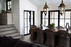 Deux lanternes en métal doré installées au-dessus d'une table en chêne vieilli sur mesure. Autour de la table, huit fauteuils en rotin. Plancher rustique européen. Chandeliers en métal et pot de fleur en ciment.
