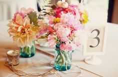 love little mason jars as vases. and the mirrored votive. aaand love the idea of table numbers printed on book pages.
