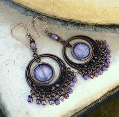 A lovely pair of bohemian chandelier earrings in lavender, mauve, purple and antique copper.    Dangles of glass beads and a czech glass centrepiece