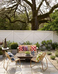 In a Napa Valley cottage decorated by Ken Fulk, the sweet sitting area has a colorful mix of accessories. Vintage metal glider and chairs from Zonal. Pillows from Pottery Barn. Victoria Pearson  - HouseBeautiful.com