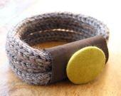 Bracelet fait de plusieurs tours de tricotin maintenus par un tube de tissu orné d'un gros bouton.