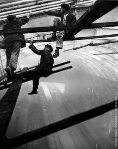 High above the trains, painters at work inside the roof at King's Cross Station, carrying out the task of cleaning, repairing and painting the roof, a job which is carried out every seven years.  (Photo by William Vanderson/Fox Photos/Getty Images). 21st January 1936