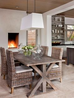 Wicker chairs, a wooden table, and a neutral color palette give this dining area an outdoorsy feel. The simple, rustic look gives off a carefree, laid-back tone and creates a comfortable and inviting atmosphere. A gas firepla