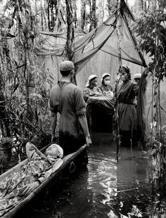 1970 - Vo Anh Khanh, a Cambodian guerrilla, is carried to an improvised operating room in a mangrove swamp in this Viet Cong haven on the Ca Mau Peninsula.