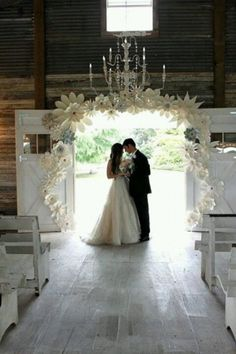 Love the cream and white flower paper arrangements surrounding the barn door with the chandelier overhead. It's rustic-country meets sophisticated glamour!  Intimate And Lovely Inside Barn Wedding Reception