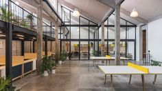 Mexican architects Estudio Atemporal has paired concrete columns and cinder block walls with black metal and glass partitions when transforming a former industrial factory in Mexico City into this co-working space.