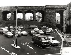 A view of Dean Street Car Park Newcastle upon Tyne taken in 1973.car park in the foreground with the railway bridge behind. The Tyne Bridge through one of the arches in the bridge.