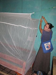 Until new nets are available, Peace Corps Volunteer Jean DeMarco works in the rural areas of Ethiopia with a local Health Extension Worker to install preexisting nets.