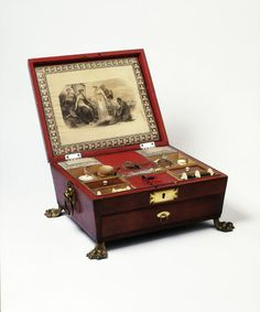 """1815 Work Box at the Victoria and Albert Museum, London - """"Work boxes, containers for sewing and embroidery tools and materials, often had many small compartments, which helped to keep the contents tidy. This box also has a drawer at the front, which opens by pulling a hidden catch. This is an expensive example, with its leather cover and silk lining. Many work boxes were simpler, comprising plain veneered wood."""""""