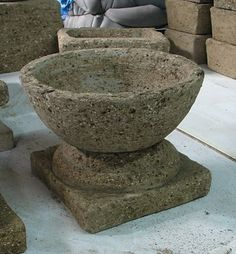 Use stepping stone as base, small bowl big enough to set urns on.