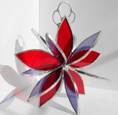 """I have been making these Flower Twirls for years and years. Now with some """"nudging"""" from my customers they are being offered here on Etsy. This stained glass flower twirl in red and purple is made from transparent glass. Each flower measures 5"""" wide and 3"""" deep and has 15 petals. The majority of Flower Twirls I make consist of 2 or more colors. The blending of the colors in sunlight is such a delight. Flower Twirls start with cutting out the petals, copper foiling them and then soldering…"""