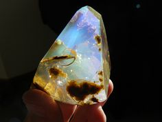 "740ct opal butte crystal with Contra luz color plays. This gem has all faceted faces and contains some amazing matrix inclusions. The mix of of facets, color plays, and minerals creates an almost mystical or ""underwater"" like scene within."