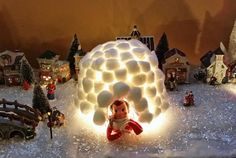 A clean milk carton, clear plastic cup, about 100 cotton balls, hot glue and a strand of Christmas lights made this Elf Igloo a huge hit in...