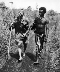 "An Australian soldier, George ""Dick"" Whittington, is aided by Papuan orderly Raphael Oimbari, at the Battle of Buna-Gona. - New Guinea during World War II 18  Best of Web Shrine"