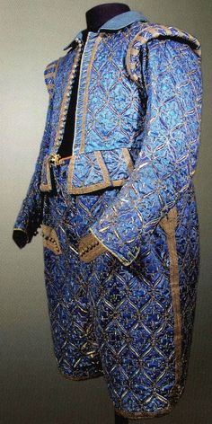 """Description by Ninya Mikhaila: """"The suit is made from blue satin, slashed to reveal ivory fabric (silk I think) behind. The patterned decoration is made with couched gold cord and the braid that edges the tabs etc is gold and blue silk woven together. One of the most interesting details we spotted when we […] looked up the legs of the breeeches […] was that they have a lining which hangs free from the leg and which […] is padded around the lower leg to maintain the open shape of the…"""