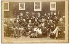 Cabinet photograph of the participants in the performance of Romberg's Toy Symphony at St. James's Hall in aid of the Children's Hospital in Great Ormond Street [14 May 1880]; (front row seated on floor) Arthur Sullivan (cuckoo) and Henry Leslie (conductor) Photo by F. A. Bridge, 9 Dalston Lane, London, 1880