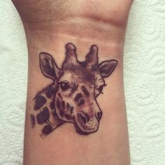 Small, girly, giraffe tattoo on wrist. In black and white