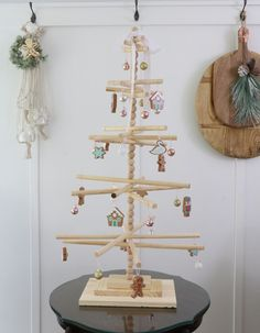 This wooden dowel Christmas tree has that minimalist look I adore with a Scandinavian vibe. It is simple to assemble and will add a fun look to your Christmas decor. Start with the base of the Christmas tree by measuring and cutting three pieces of plywood to make the base (3 1/2″ x 6″, 5″ x 9″, 8 1/2″ x 12 1/2″) and sand the edges. Next glue the middle board to the bottom board placing the middle board in the center and then nail the two boards.And then glue the top board to the m…