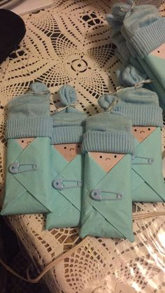 I made these baby shower favors, all you need is Hershey bars, beverage napkins, baby socks, plastic mini safety pins, and plastic mini pacifiers. And you can print out the baby faces online. Super cute