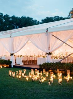 Dont forget to illuminate the outside of your space too—especially if youre pitching a tent in the middle of a dark field! Here, Tara Guérard Soirée lined the edges of this white-draped tent with pillar candles in tall glass vases.