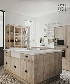 Katty Schiebeck kitchen. Fantastic tiled floor; pale wood cupboards with dark handles; pale counters.