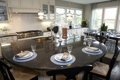 This kitchen separates the eat-in kitchen from the dining room by exchanging white chairs for black. Starfish accents give the space a beachy feel.