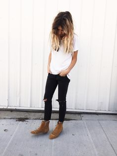 white loose oversized vneck tshirt, sunglasses hanging from neck, black knee torn skinny jeans, and camel tan ankle boots.