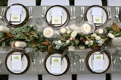 If classic acorns and pumpkins aren't your fall style, try a more subtle touch with striped feathers and brown leaves. Here, place settings showcase black-and-white feathers and brown plates, echoing the fall leaves in the centerpiece.  Via Fête Nashville