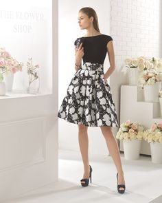 Vestido corto clásico de costura con cuerpo de crepe con cuello redondo y falda de brocado, disponible en negro/blanco.