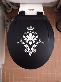 Revamp a boring toilet seat with a vinyl decal. Seal it in with Mod Podge and clear spray paint.