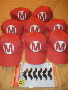 "Make Super Mario Brothers hat for cute party favors. All you need is basic red baseball hats, round felt cut outs, letter ""M"" di-cut, red paint, and fabric glue. Don't forget to get the stick on mustaches."