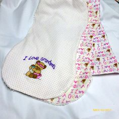 This blanket is made from a single layer of flannel with pink and lavender I Love Grandma and little bears. The first burp cloth is made from the same fabric as the blanket and the second is made from pink polka dot flannel and has a little bear holding a bottle and I Love Grandma embroidered on it, both have Terri cloth on the back side to absorb any messes. The blanket measures approx. 33 square and the Burp Cloths are approx. 10x17 with a contoured center. The set comes tied with a tulle…