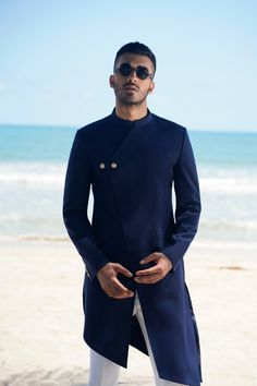 #TheIsleOfSummer | Indulge in signature creations crafted with intricacy and artistic expression. The Navy Blue Asymmetric Sherwani with an angular hem and tab detail is just the right option to make a statement at any occasion. #SSHOMME #SarahAndSandeep #TheIsleOfSummer #SummerFestive #Menswear #Mensfashion #HauteCouture #Resortwear #Islandfusion Wedding Kurta For Men, Wedding Dresses Men Indian, Wedding Dress Men, Mens Indian Wear, Mens Ethnic Wear, Indian Groom Wear, Nigerian Men Fashion, Indian Men Fashion, Mens Fashion Suits