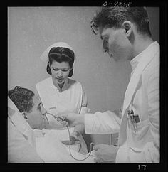 Nurse training in history. A student nurse aides the doctor in a gastric analysis. From 1942