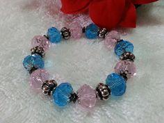 Pulseira confeccionada em fio de silicone com cristais azuis e rosa 14mm, tulipinhas em níquel, entremeios em níquel envelhecido e hematita.