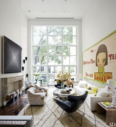 1965 Frank Stella canvas hangs over the mantel, while a painting by Yoshitomo Nara dominates the opposite wall.